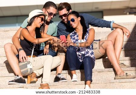 Outdoor portrait of group of friends having fun with smartphones