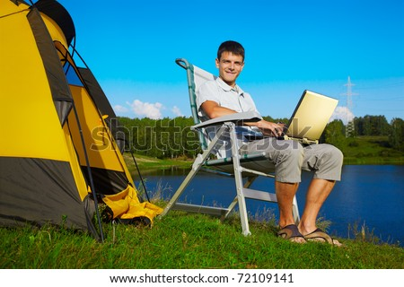 outdoor portrait of handsome man with laptop sitting in folding chair near camp tent