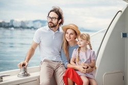 Outdoor portrait of happy family with 4-year old daughter on sailing boat at sunny summer day. European parents playing with kid on a bow of luxury yacht. Family, Marine Cruise and people concept