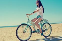 Outdoor portrait of happy woman biking in city park. Joy and happiness. Venice Beach