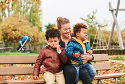 Outdoor portrait of happy young mother with two lovely sons, family enjoying nice autumn day in public park, mixed race family. Kids eating snacks, resting on bench