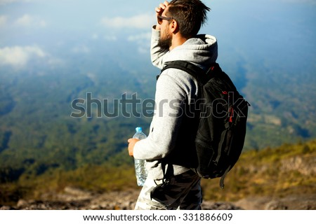 Outdoor portrait of hiker man posing on the mountain,freedom concept.tourist looking at dramatic river.Man hiker looking at landmarks in forest nature.Ascent to the volcano,travel guide,equipment