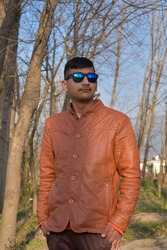outdoor portrait of indian ethnicity boy looking sideways wearing blue sunglasses and brown leather coat.