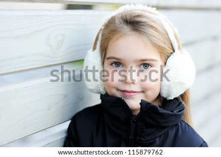 Outdoor portrait of little girl wearing white earmuffs