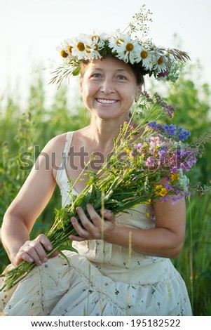 Outdoor portrait of mature  woman in camomile wreath