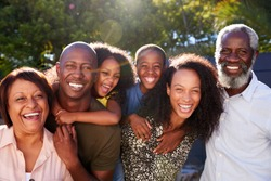 Outdoor Portrait Of Multi-Generation Family In Garden At Home Against Flaring Sun
