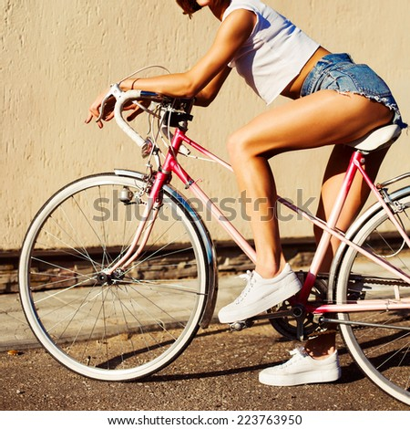 Outdoor portrait of pretty sexy young tanned sport style hot legs woman posing on pink bicycle on creamy wall background