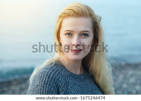 outdoor portrait of pretty smiling blonde young woman in gray knitted sweater looking at camera, morning nature background ストックフォト ©