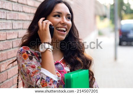 Outdoor portrait of pretty student girl talking on the phone