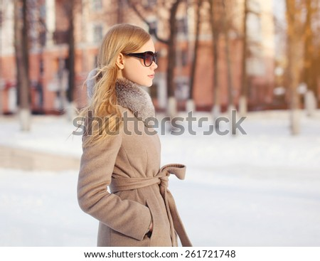 Outdoor portrait of profile beautiful elegant woman dressed a coat and sunglasses in the park
