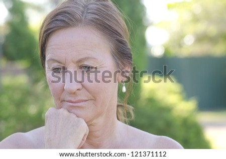 Outdoor portrait of sad and worried looking mature woman, isolated with blurred background