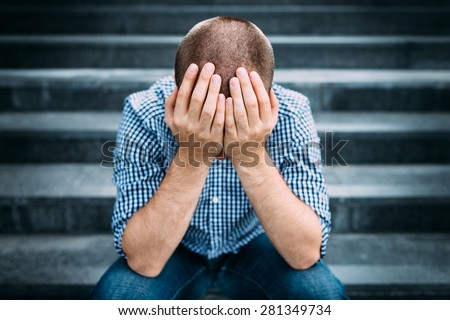 Outdoor portrait of sad young man covering his face with hands sitting on stairs. Selective focus on hands. Sadness, despair, tragedy concept