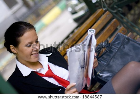 outdoor portrait of smiling businesswoman reading magazine