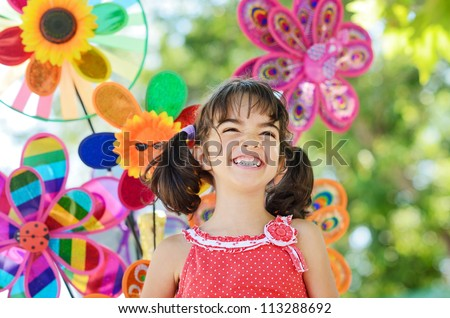 Outdoor portrait of smiling little girl over colorful pinwheel background