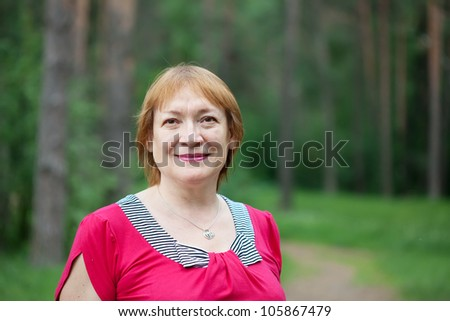 Outdoor portrait of smiling mature woman - stock photo