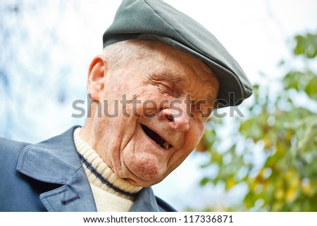Outdoor portrait of smiling senior man in hat