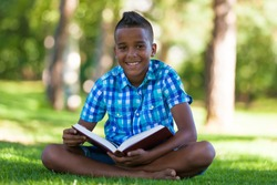 Outdoor portrait of student black boy reading a book - African people