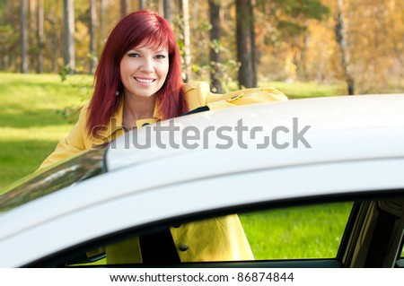 Outdoor portrait of successful cute young woman standing by her new car