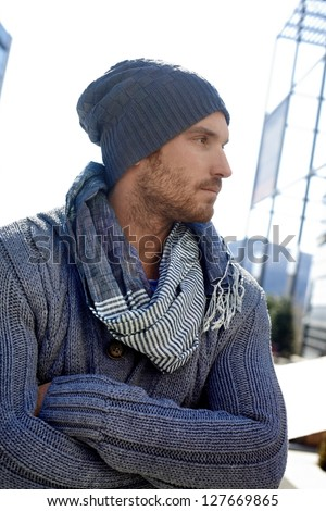 Outdoor portrait of trendy guy wearing scarf and hat, arms crossed. - stock photo