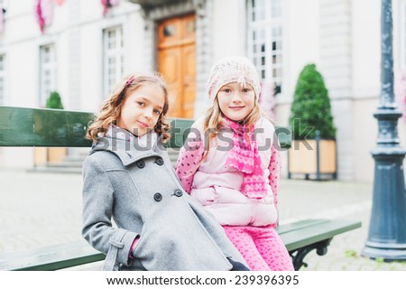 Outdoor portrait of two adorable little girls of seven years old, resting on the bench in a city