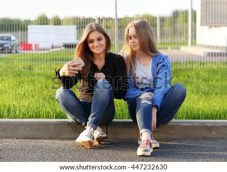 Outdoor portrait of two cheerful girl using smartphone. #447232630