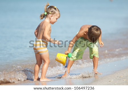 outdoor portrait of two children playing with water on sand beach
