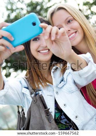 Outdoor portrait of two friends taking photos with a smartphone
