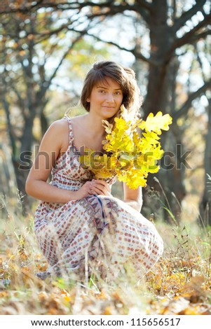 Outdoor portrait of  woman in autumn with oak posy