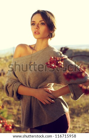 outdoor portrait of young beautiful, attractive, sensual female posing in field and looking side way.