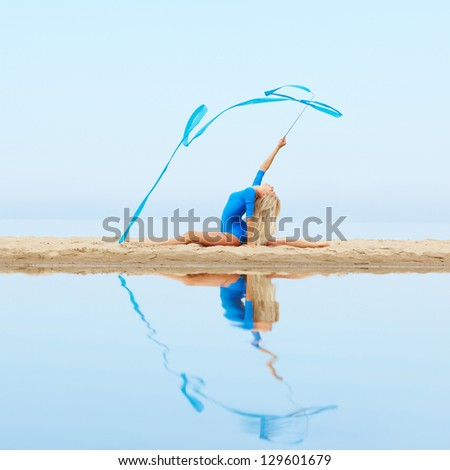 outdoor portrait of young beautiful blonde woman gymnast training with ribbon on the beach
