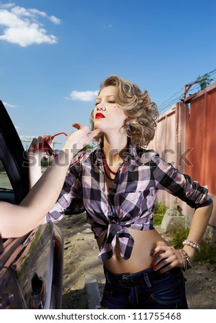 outdoor portrait of young beautiful blonde woman hitchhiker  flirting with driver