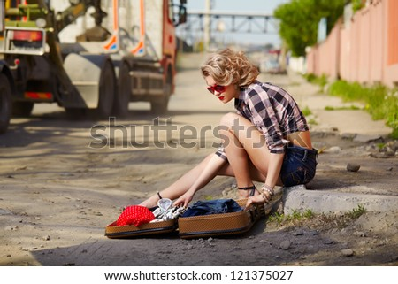 outdoor portrait of young beautiful blonde woman hitchhiker sitting on the roadside and opening suitcase