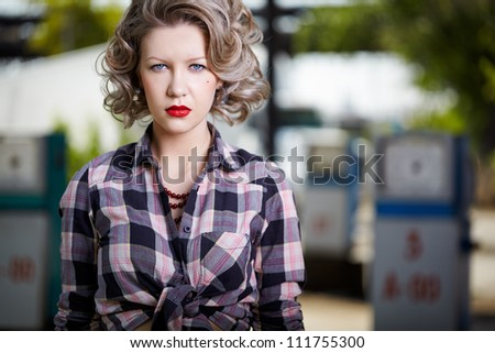 outdoor portrait of young beautiful blonde woman posing  on gas station with petrol pumps on background