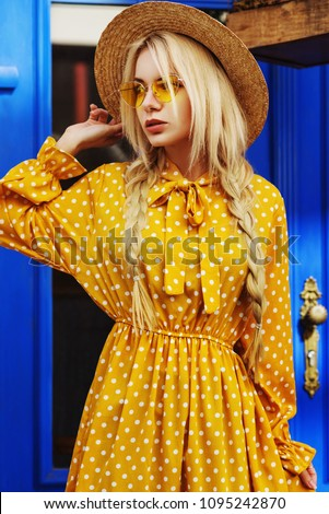 Outdoor portrait of young beautiful fashionable girl wearing trendy yellow color sunglasses, straw hat, polka dot dress posing in street of european city. Blue background. Summer fashion concept #1095242870