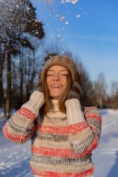 Outdoor portrait of young beautiful fashionable happy smiling woman winter portrait, woman in winter hat, snow. enjoying winter moments