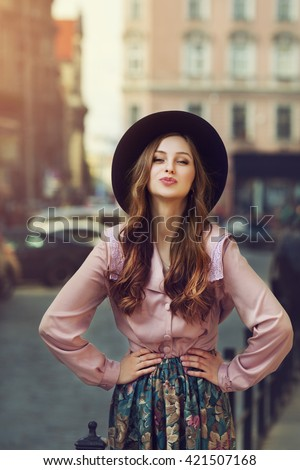 Outdoor portrait of young beautiful fashionable playful lady posing on old street. street. Model wearing stylish hat & clothes. Sunny day. Female fashion. City lifestyle. Toned style instagram filters