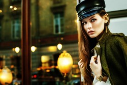 Outdoor portrait of young beautiful fashionable woman posing in street. Model wearing stylish leather hat, green jacket. Lights and reflections on background. Copy, empty space for text