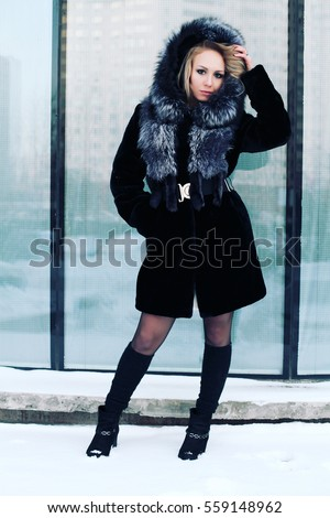 Outdoor portrait of young beautiful fashionable woman posing on street. Model wearing stylish winter fake fur coat and snowy furry hood, leather bag, suede boots. Photo toned style instagram filters. #559148962