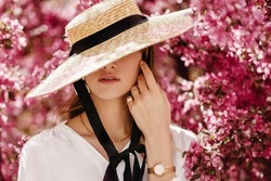 Outdoor portrait of young beautiful fashionable woman wearing stylish accessories: hat, wrist watch, rings. Hidden eyes with hat. Female fashion, beauty and advertisement concept. Copy space for text