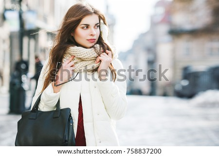 Outdoor portrait of young beautiful fashionable woman wearing stylish white winter puffer coat, scarf, holding leather tote bag. Model walking in street. Female fashion concept. Copy, empty space - Shutterstock ID 758837200