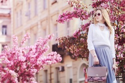 Outdoor portrait of young beautiful girl posing in street of european city, blooming trees on background. Model wearing stylish sunglasses, holding pink bag. Female fashion concept. Copy, empty space