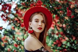 Outdoor portrait of young beautiful girl with red lips, long blonde hair, wearing hat, long tassel earrings, cold shoulder dress, posing near blooming tree. Summer fashion concept. Copy space