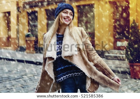 Outdoor portrait of young beautiful happy smiling girl posing on street. Model wearing stylish warm clothes. Magic snowfall. Christmas, new year, winter holidays concept. City lifestyle. Waist up