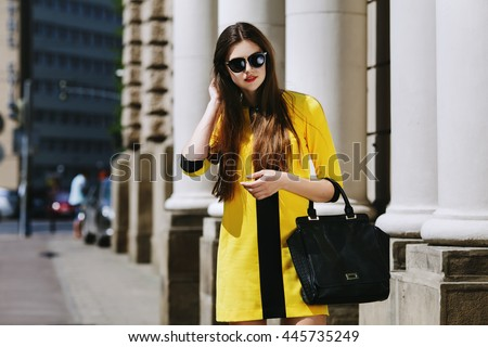 Shutterstock Outdoor portrait of young beautiful lady walking on the street. Model wearing sunglasses & stylish yellow summer dress. Girl looking down. Female fashion concept. City lifestyle. Sunny day. Waist up