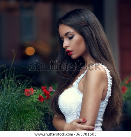 Outdoor portrait of young beautiful stylish woman with long dark hair and red lips posing in white lace top. Art fashion portrait of pensive or thoughtful girl with shallow depth of field #363981503