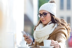 Outdoor portrait of young beautiful woman using her mobile phone in a cafe.