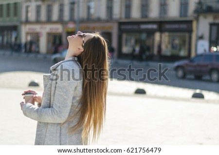 Outdoor portrait of young beautiful woman with long hair , coffee to go and sunglasses, looking at the sky #621756479