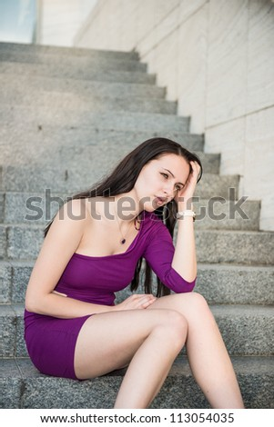 Outdoor portrait of young beautiful worried woman sitting on stairs