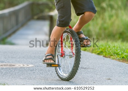 outdoor portrait of young boy riding a unicycle (one wheel bike) on natural background - Shutterstock ID 610529252