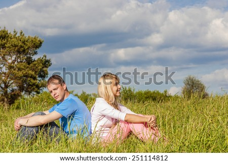 outdoor portrait of young couple sitiing on green grass back to back